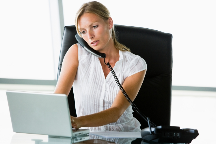 Businesswoman sitting in office with laptop on telephone